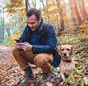 man in woods on phone with dog